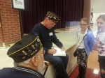 Post 182 Member signing a book for a student